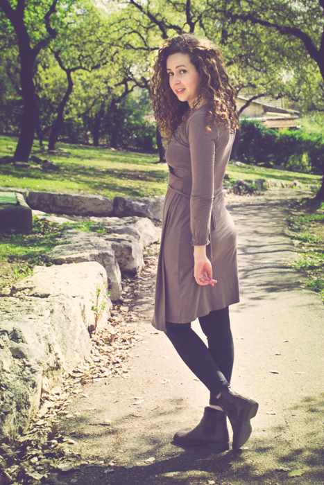 curly haired brunette in a brown dress and boots looking back while walking down a dirt path in a park - cropping photos