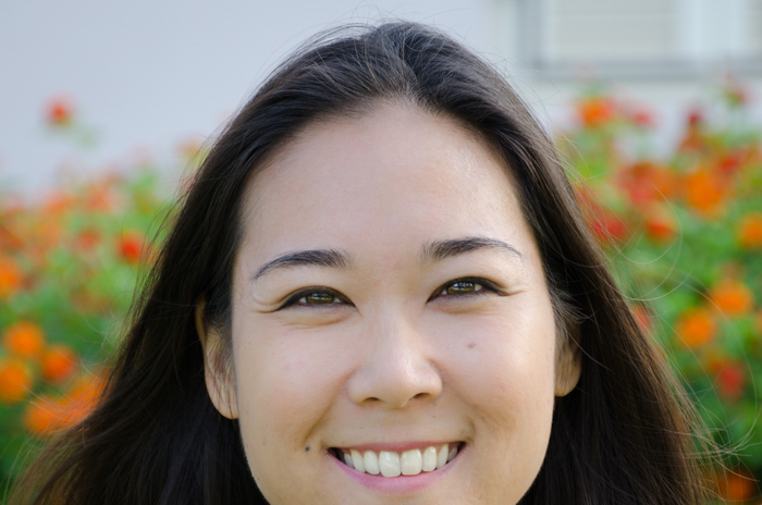 cropped headshot of smiling asian woman in a field of red flowers