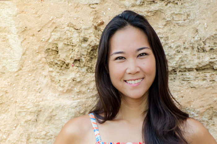 photo cropped below shoulders of smiling asian woman in front of a sandy stone wall