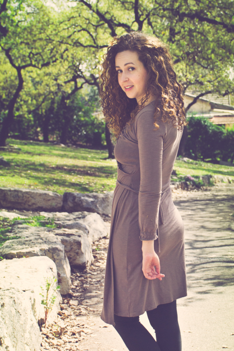 cropped photo of curly haired brunette in a brown dress and boots looking back while walking down a dirt path in a park