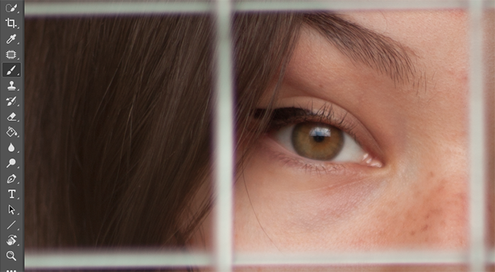 A close up of a girls eyes with a fence in front of her open for editing