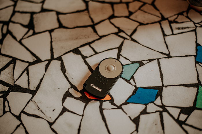 A canon camera remote on a tile floor