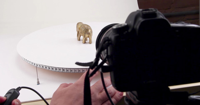 A DSLR camera set up in front of an ornament of an elephant on a lazy susan - diy photography shoot