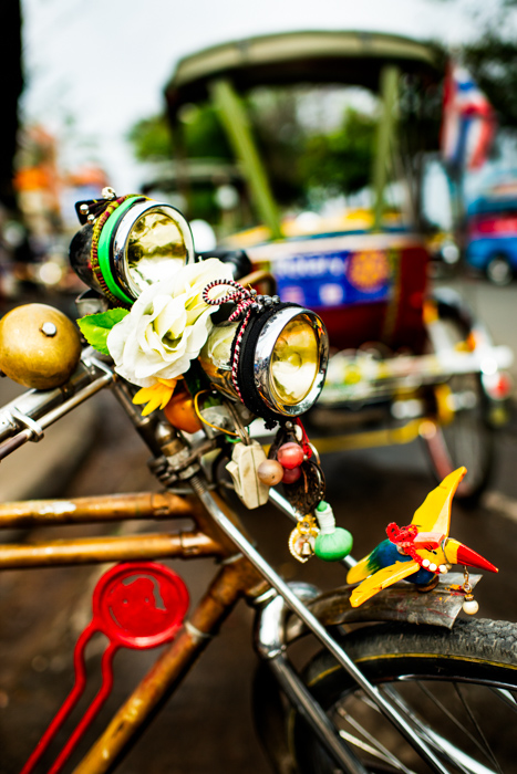 A close up of a bicycle light, adorned with brightly colored decorations - documentary photography tips