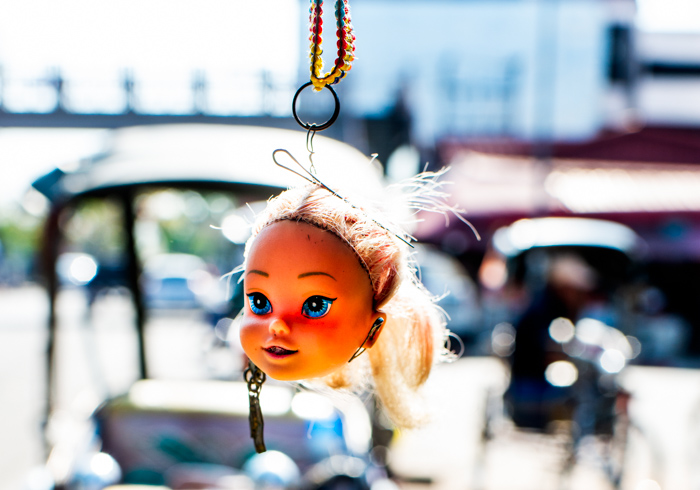 A dolls head hanging from a car or bike