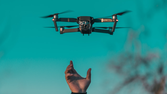 A persons hand reaching up to a low flying drone