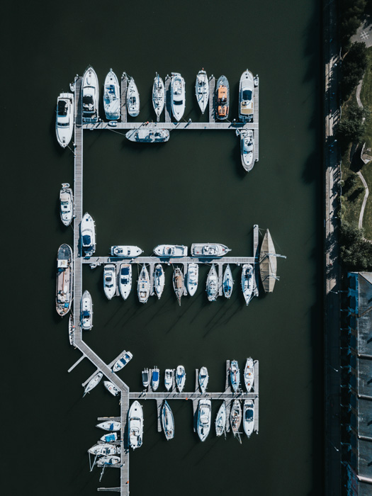 An aerial view of a boats parked in a harbour taken with a drone