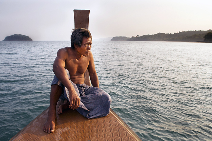 A man sitting on a small wooden boat at sea