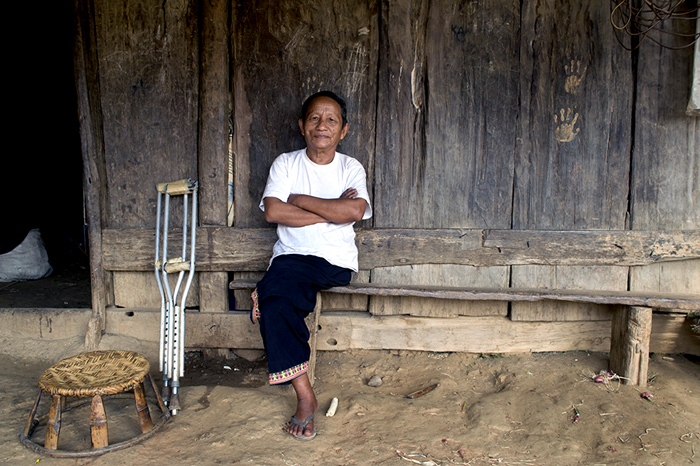 A Hmong man sitting outside his wooden house - editorial portrait photography tips