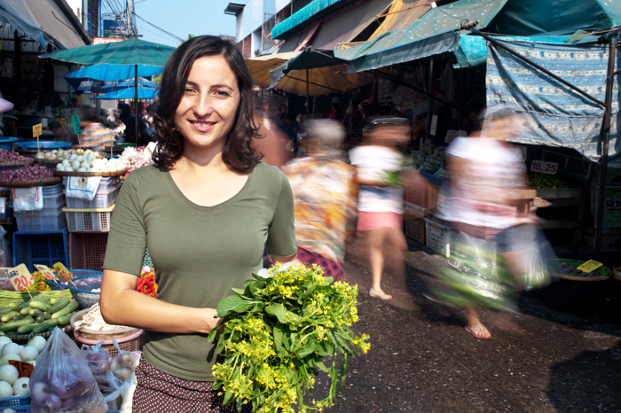 Young woman standing in a busy market. Shot using a slow shutter speed to get the movement of the people blurred.