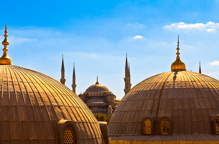 Golden domes of the Hagia Sophia, an ancient Byzantine structure, in Istanbul, Turkey, against a clear bright blue sky