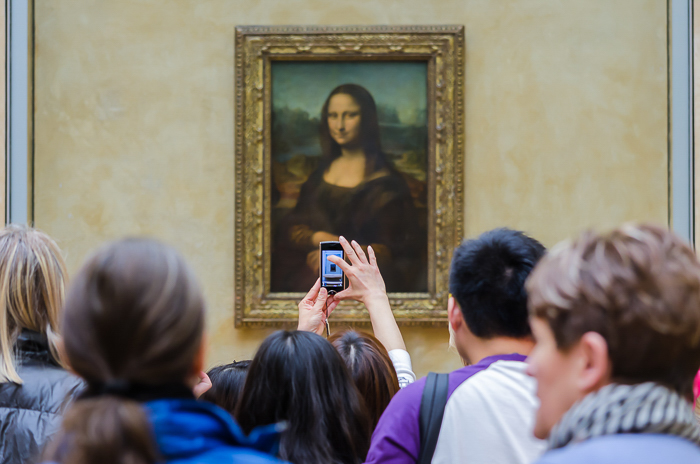 People looking at the Mona Lisa in the Louvre and someone taking a photo on a smartphone