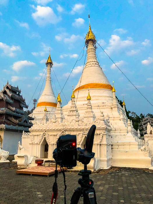 camera on tripod ready to photograph Bhuddist stupa against a bright blue sky in the early morning