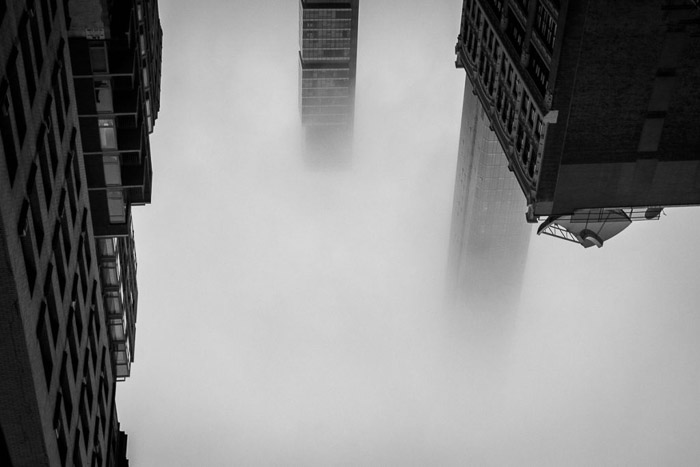 Atmospheric shot of three buildings emerging from Manhattan in fog. New York, NY, USA