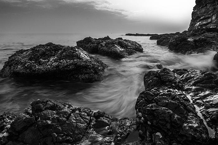 Une photographie d'art en noir et blanc d'une plage rocheuse, avec un doux effet brumeux de l'eau autour des rochers et des falaises