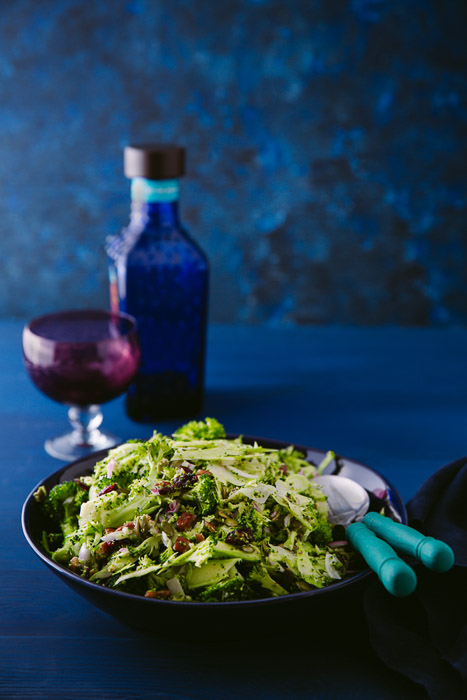 A bowl of shaved brocolli salad, balsamic veingear and a small glass on a dark blue background