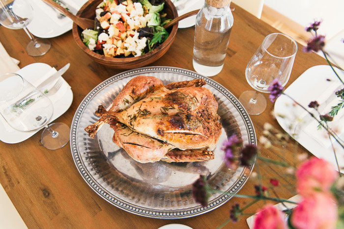 Overhead shot of a roast chicken and other dinner items