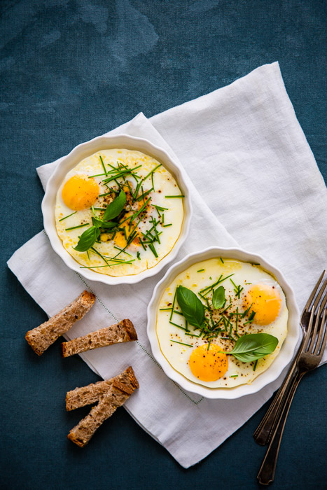 Overhead food styling shot of baked eggs in two white bowls against a dark blue background