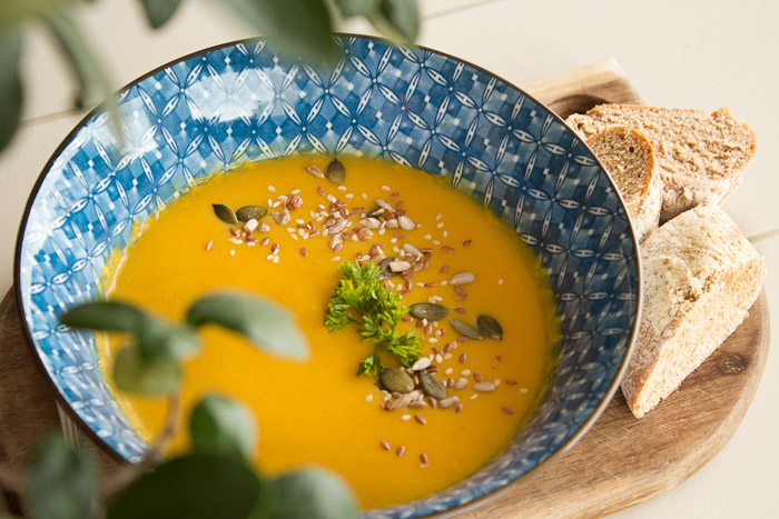 Overhead shot of orange soup in abowl, with bread and leaves beside it