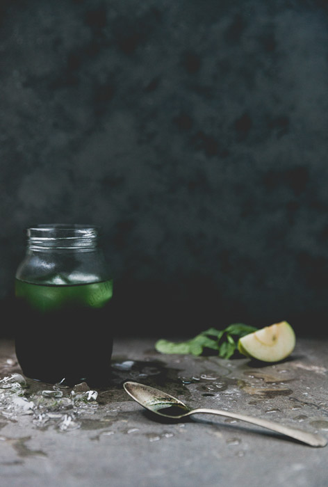 A still life featuring a green drink in a jar beside a teaspoon and ingredients against a dark background