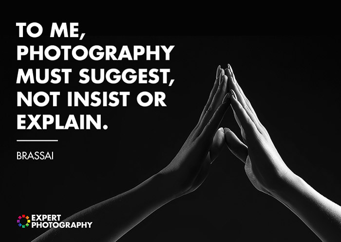 A black and white close up shot of two hands touching overlayed with a quote from Brassai on what makes a good photograph