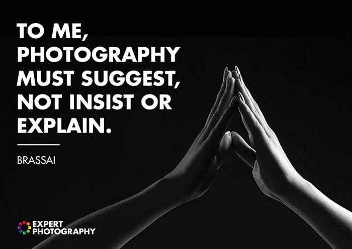 Um close preto e branco de duas mãos tocando sobreposto com uma citação de Brassai sobre o que faz uma boa fotografia.