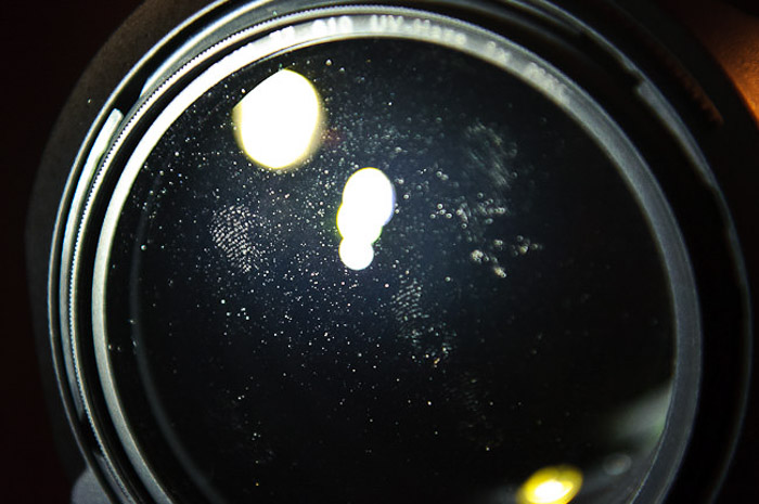 A close up of a camera lens which is dusty and smudged with finger prints