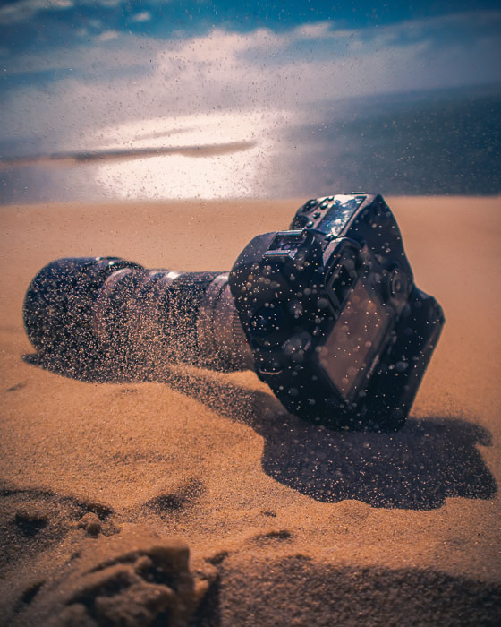 A DSLR camera resting on the sand at the beach - how to clean camera lens