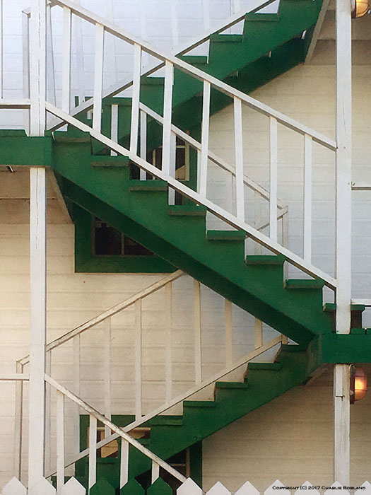 A green outdoor stairway, the diagonal lines creating a Z pattern taken with iPhone photography camera