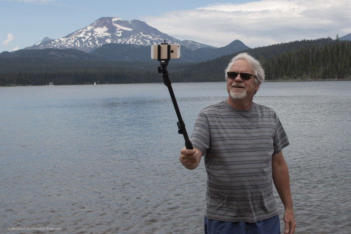 A man taking iphone photo of himself with a selfie stick