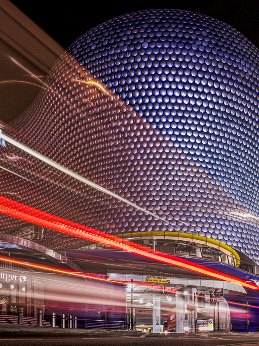The Bullring Shop Center in Birmingham with the light trails from a double decker bus passing in front