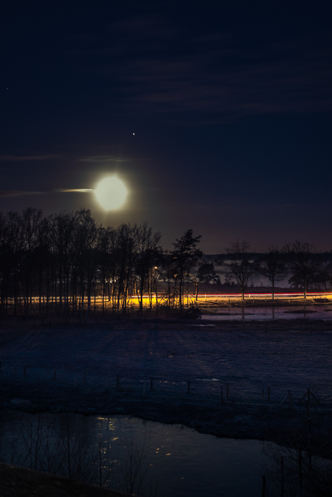 Light trails in a winter night under a full Moon (with Jupiter next to it).