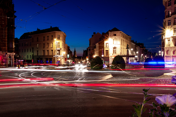 Urban scene with many light trails going all in different directions making a confusing image.