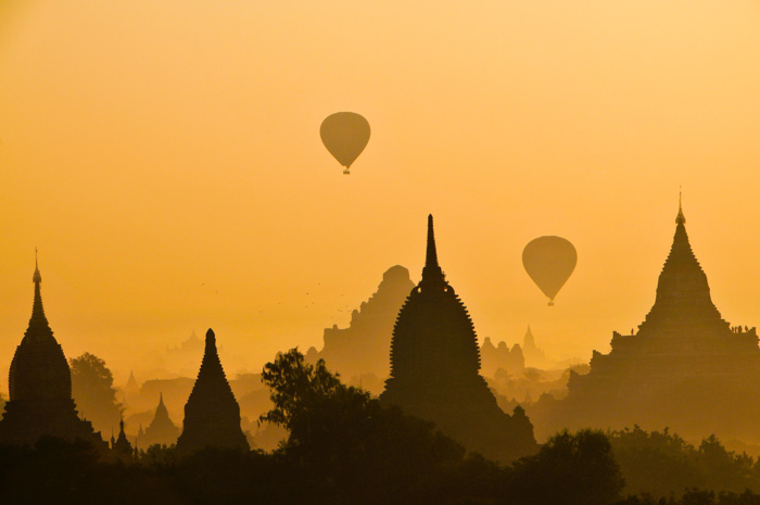 A beautiful evening shot of hot air balloons flying over a city silhouette