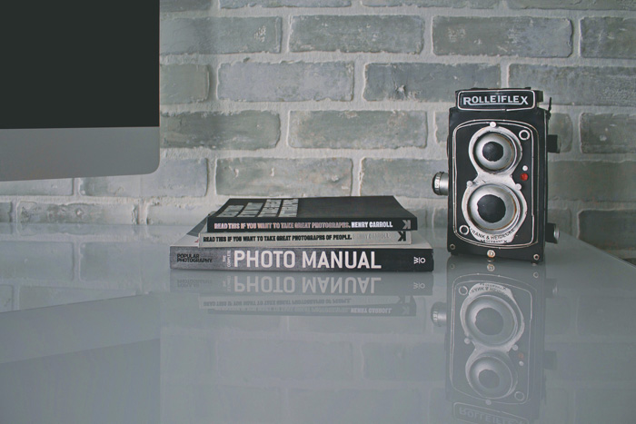 a roliflex camera and photography books resting on a table - manual camera settings