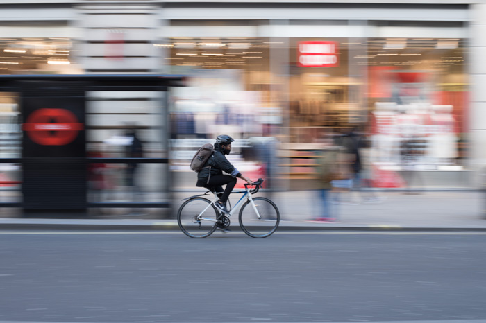 A cyclist riding down a roadway with blurry background behind - using camera manual mode