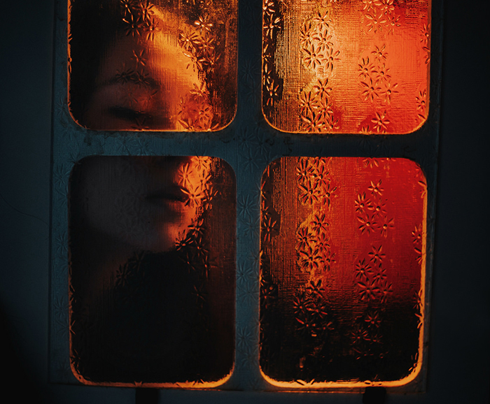 Atmospheric portrait of a girl with face pressed against a window pane with ambient lighting