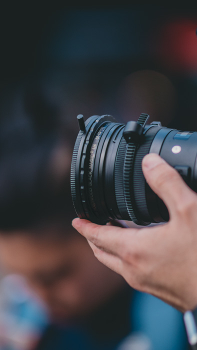 Close up of a photographer holding a DSLR camera with an ND filter fitted