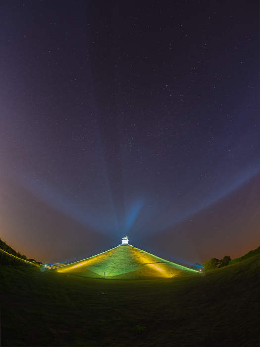 photo of La Butte Du Lion, Waterloo in Belgium, brightly lit in green and yellow, under the dark sky littered with stars.