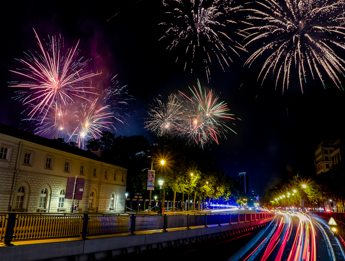 an urban street and building lit by colourful fireworks and light trails from vehicles on the street against a dark night sky