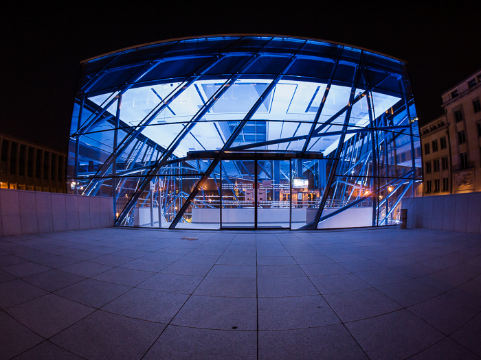 Night photo of a geometric structure lit from inside with an electric blue light.