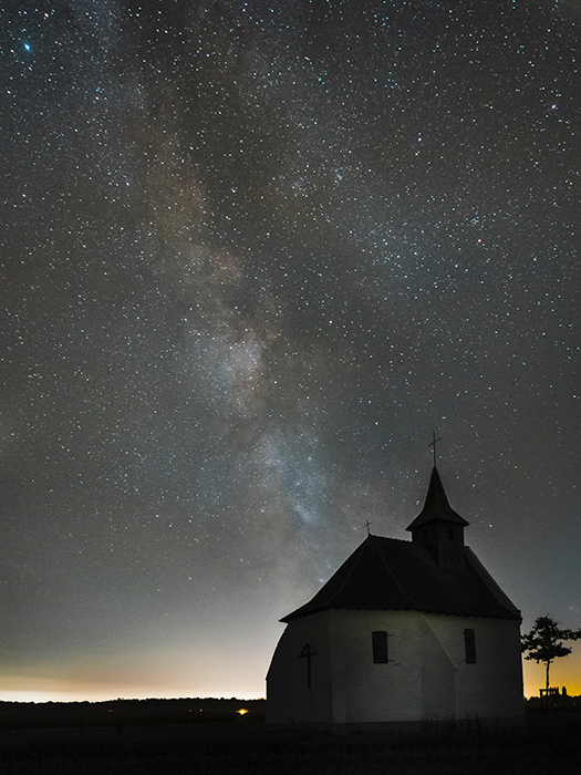 a chapel on a hill lit warmly from behind, against the night sky with the milky way visible