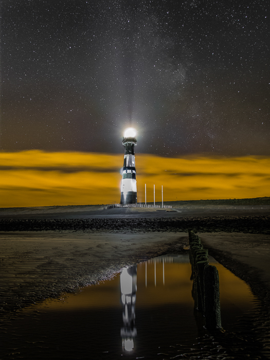 a lighthouse in the netherlands, yellow lit clouds in the background, reflected in a pool of water on the beach
