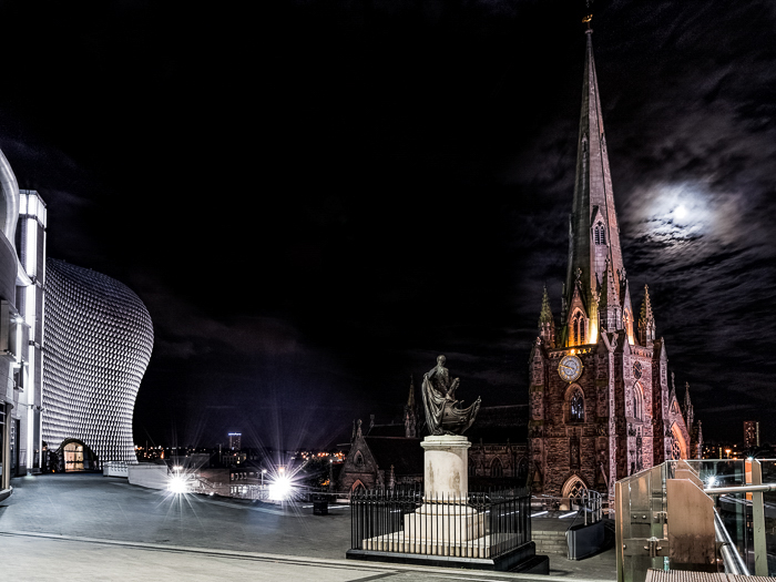 St Martin in Bullring, with the Nelson statue and the Bullring shop centre in Birmingham. The structure lit against a dark sky, the moon eerie behind clouds