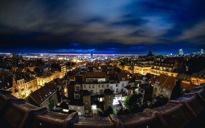 Paisagem urbana de uma cidade suburbana iluminada por luzes amarelas, um horizonte azul elétrico contra um céu noturno nublado