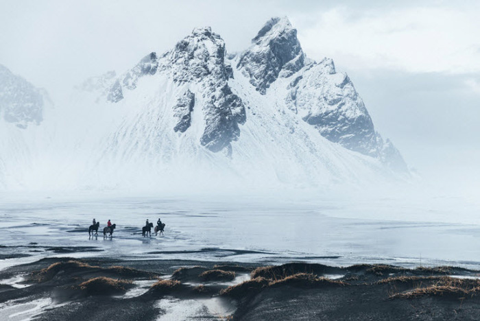 Four people on horseback trekking through an icy mountainous landscapes