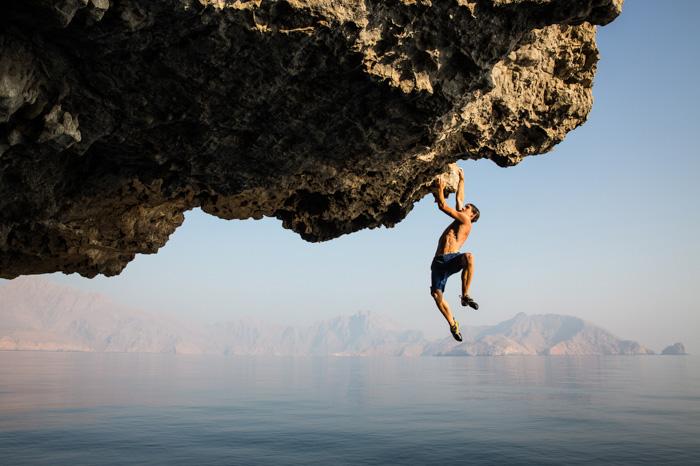 Adventure photography shot of a man rock climbing above a beautiful seascape - famous nature photographers