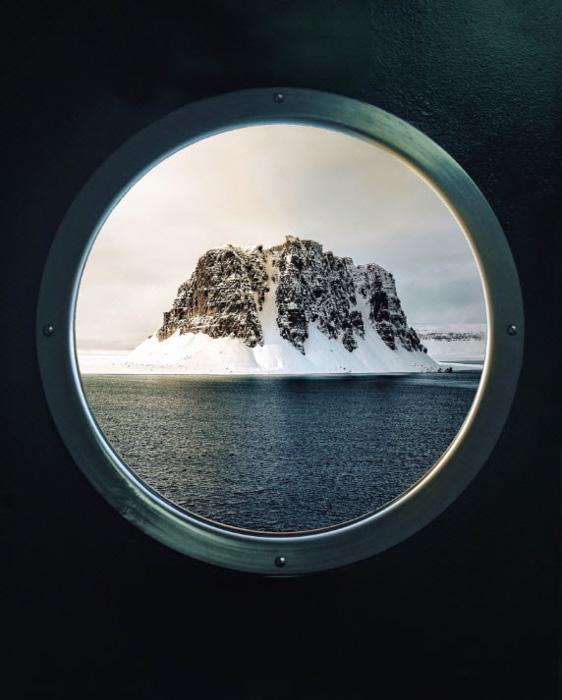 An iceberg shot though a ships porthole by Simone Bramante