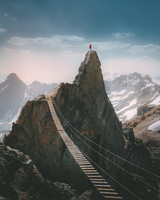 Amazing mountainous landscape with a person standing on a high peak in the background by Jame Justus Out