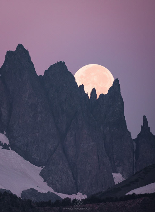 A majestic mountainous landscape in low light, the moon behind the mountains by famous photographer Joshua Cripps